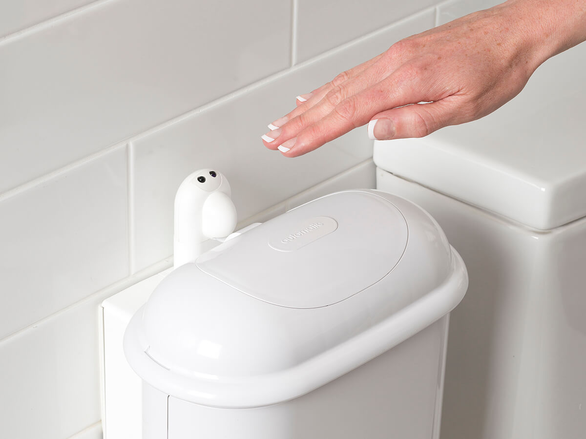 A person holding hand over Pod Petite Auto sensor to activate touch-free opening