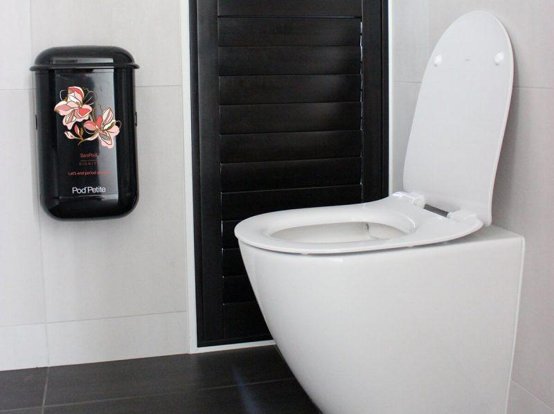 A black Pod Petite sanitary disposal unit beside a toilet with a Pod Wrap SaniPod x Dignity decal.