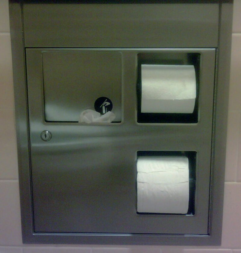 A wall recessed sanitary disposal receptacle in USA overflwoing with feminine hygiene waste