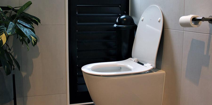 A washroom image with black Pod Classic Mini Manual unit wall-mounted on tiled wall