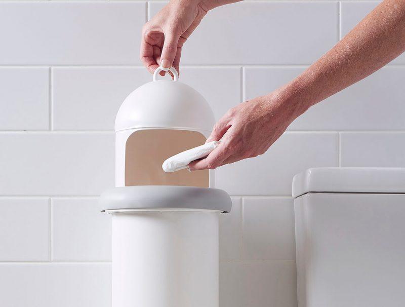 A person disposing sanitary waste into Pod Classic sanitary pad disposal manual unit