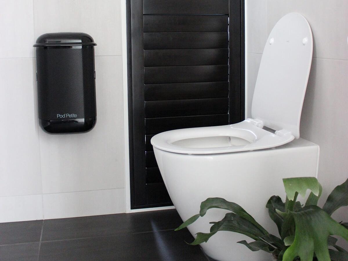 A black Pod Petite sanitary disposal unit beside toilet with a Pod Wrap Carbon Fibre decal.
