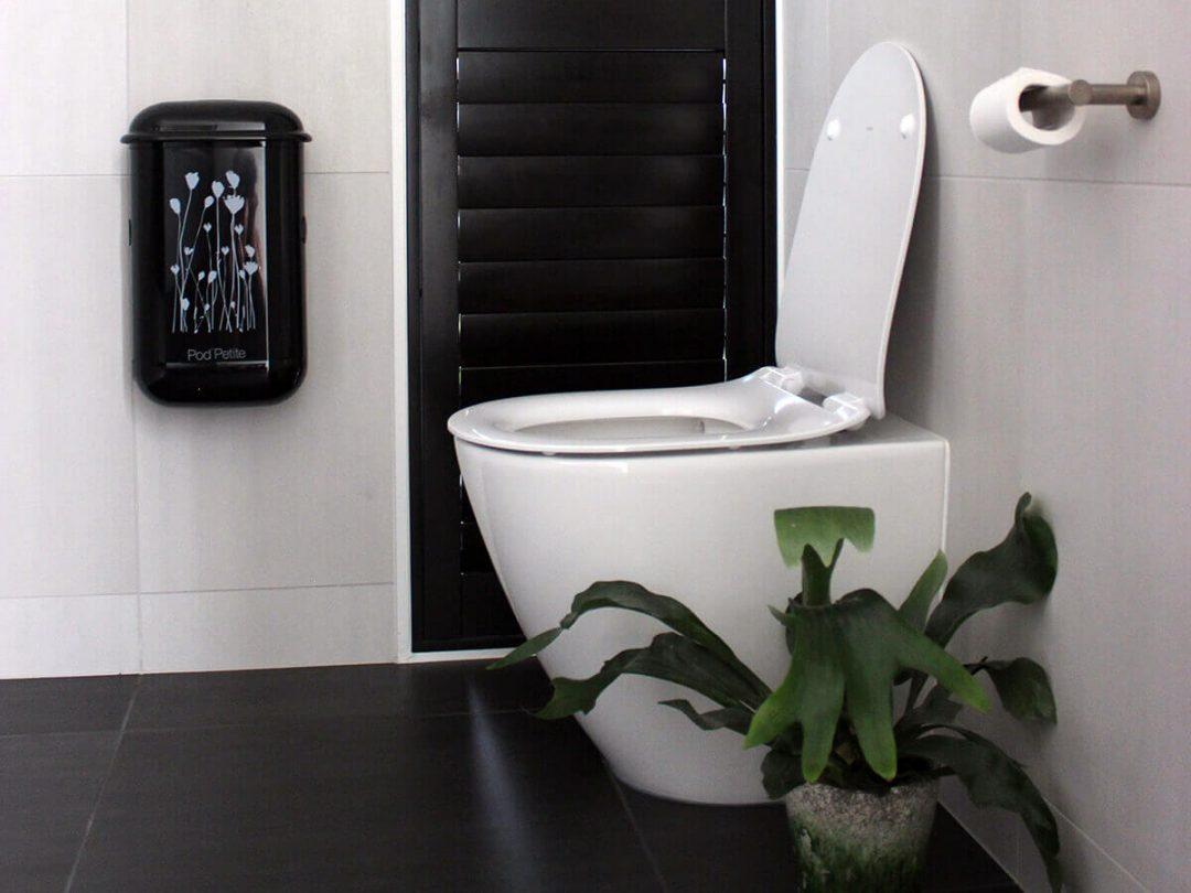 A black Pod Petite sanitary disposal unit with a Pod Wrap Poppies decal.