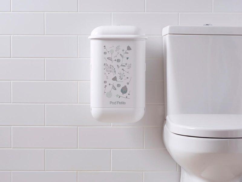 A white Pod Petite sanitary disposal unit with a Pod Wrap Woodland decal.