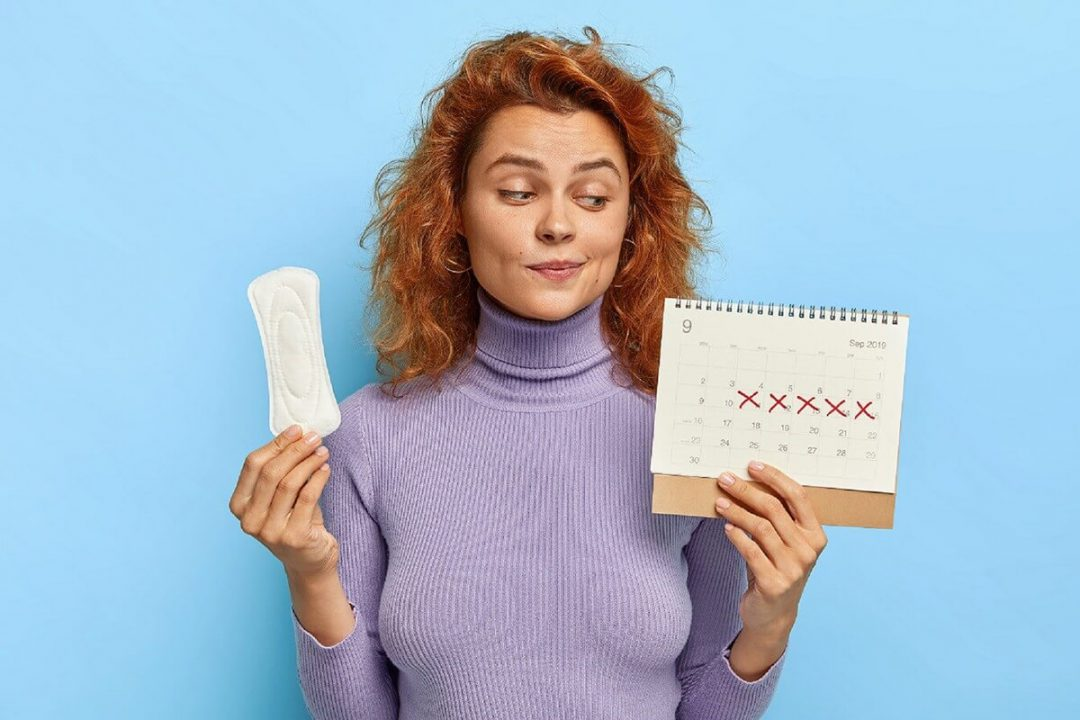 A woman holding a sanitary pad in one hand and a calendar with her period dates crossed off in another.