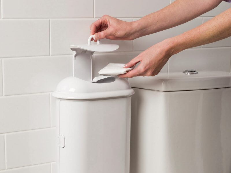 A person disposing sanitary waste into Pod Petite sanitary pad disposal manual unit