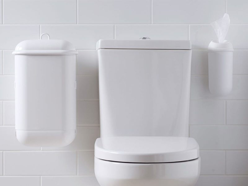 A washroom image with white Pod Petite Manual unit and white Wet Wipe dispenser installed beside toilet