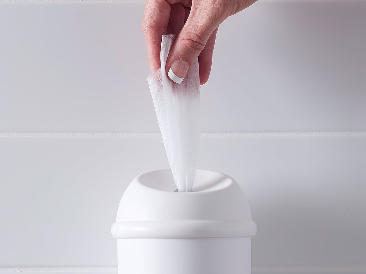 A white Wet Wipe dispenser with hand pulling antimicrobial wet wipe out
