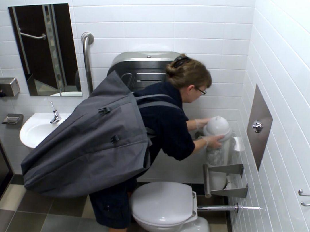 A hygiene service technician servicing a SaniPod in a washroom