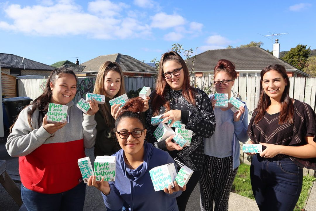 A group of women holding up period products donated from Dignity NZ