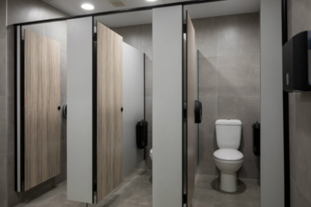 Restroom cubicles featuring black Pod Petite manual units installed in side wall