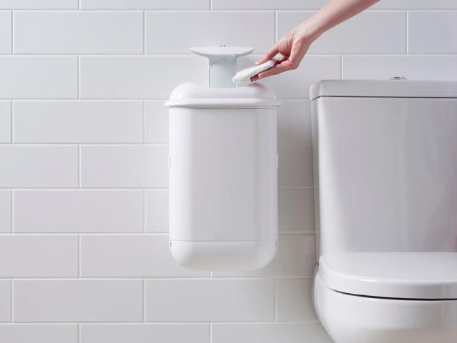 A person disposing sanitary waste into Pod Petite sanitary pad disposal automatic unit