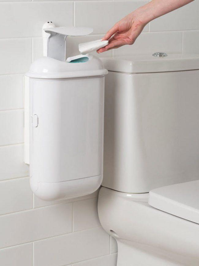 A person using a SaniPod Pod Petite white automatic unit