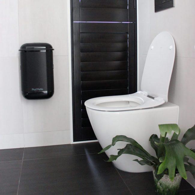 A black Pod Petite sanitary disposal unit with a Pod Wrap decal.