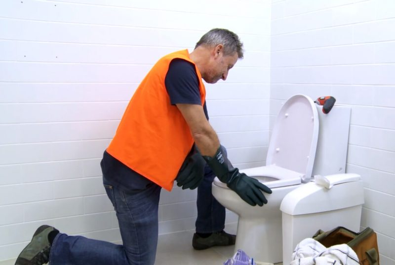 Plumber fixing blocked toilet caused by flushed sanitary waste