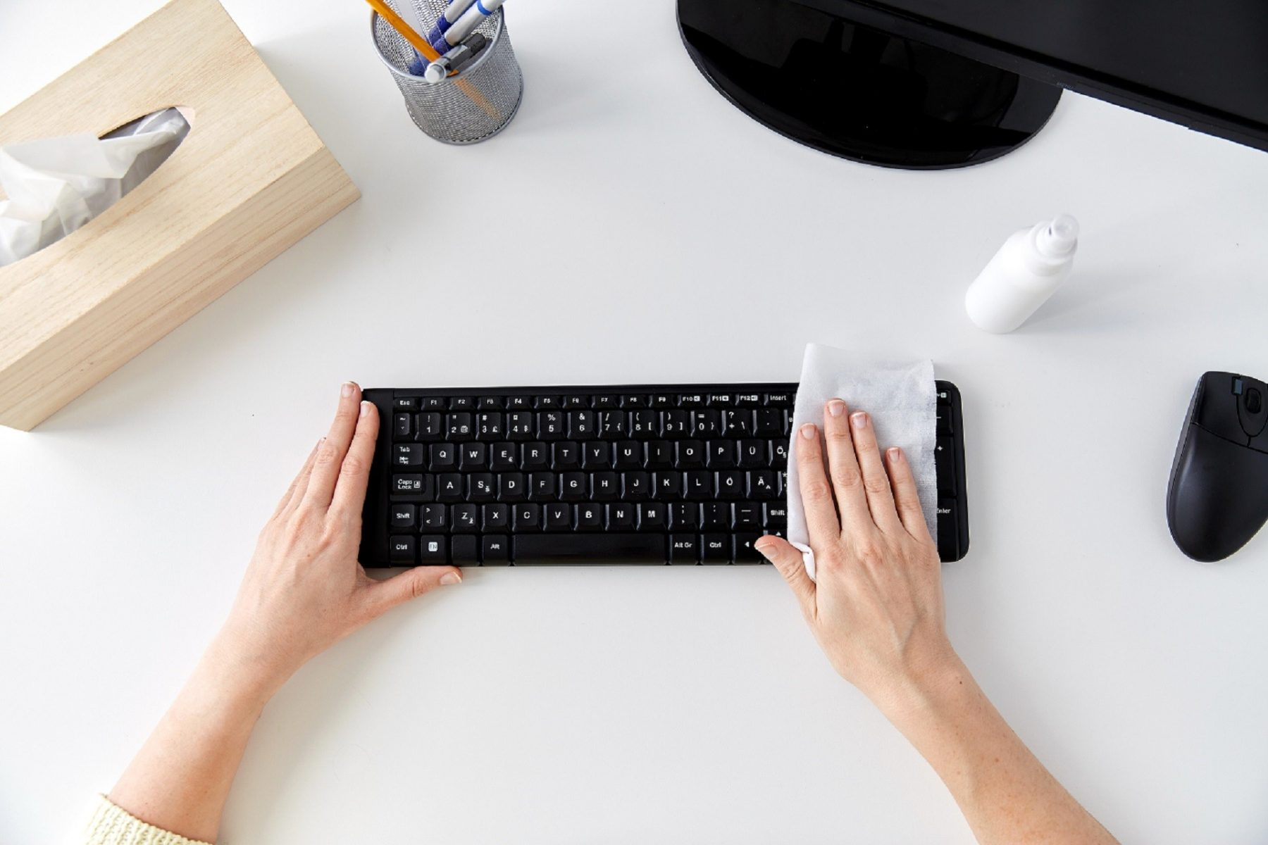 A person wiping down their keyboard with cleaning wipes